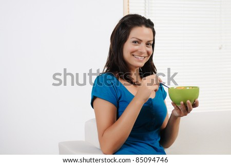 Portrait  of a beautiful young woman  having breakfast cereal  while smiling at the camera. - stock photo