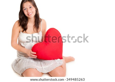 Portrait of a beautiful young woman holding a red heart pillow, in front of white studio  background, photo with copy space on the right side of the image - stock photo