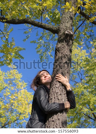 Portrait of a beautiful young woman hugging a tree in fall season  - stock photo