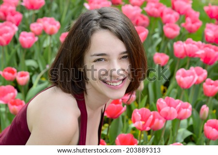 Portrait of a beautiful young woman in a pink tulip garden - stock photo