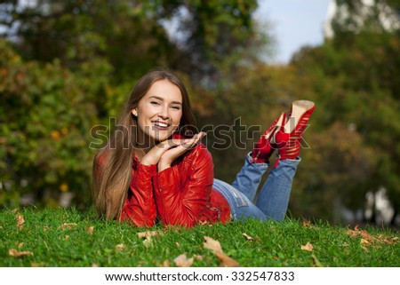 Portrait of a beautiful young woman in a red leather jacket lying on the lawn in the autumn park - stock photo