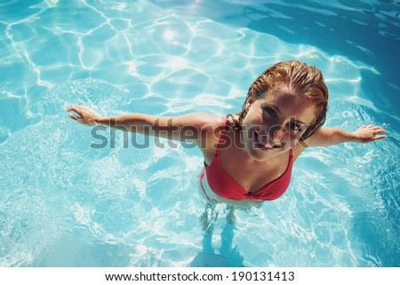 Portrait of a beautiful young woman in a swimming pool looking at camera. Pretty caucasian female model in swimwear. - stock photo