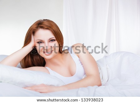 Portrait of a beautiful young woman in bed in the early morning - stock photo