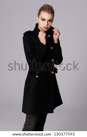 portrait of a beautiful young woman in black coat posing - stock photo