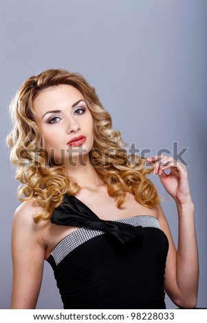 Portrait of a beautiful  young woman in black dress with curly hair - stock photo