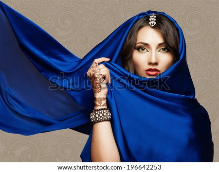 Portrait of a beautiful young woman in blue fabric - stock photo