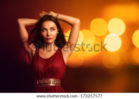 Portrait of a Beautiful Young Woman in Fashionable Red Dress over Bright Night Lights. Nightlife Party Concept. - stock photo