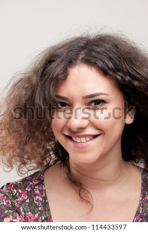 portrait of a beautiful young woman in front of a gray background - stock photo