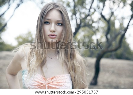 Portrait of a beautiful young woman in park. Outdoors shot, autumn style. Horizontal - stock photo