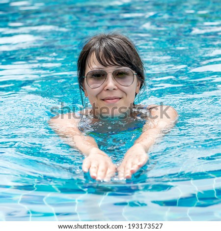 Portrait of a beautiful young woman in sunglasses floating in the pool. Concept photo healthy lifestyle - stock photo