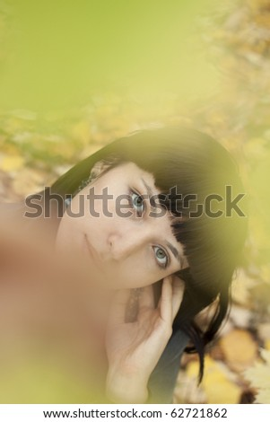 Portrait of a beautiful young woman in the autumn park. - stock photo