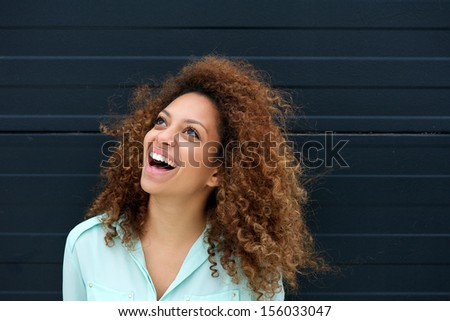 Portrait of a beautiful young woman laughing outdoors and looking up - stock photo