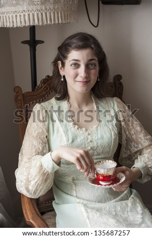 Portrait of a beautiful young woman looking directly at the camera. She is in a vintage dress and sitting in an antique chair holding her antique teacup and saucer. - stock photo