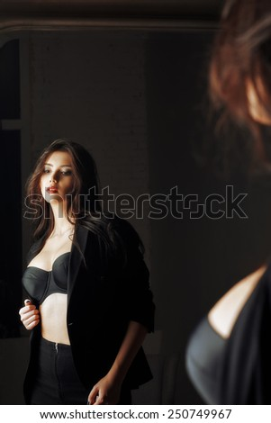 Portrait of a beautiful young woman looking into the mirror - stock photo