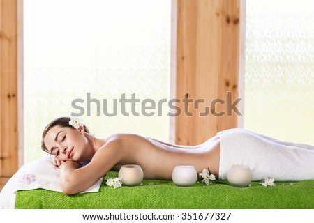 Portrait of a beautiful young woman lying on green towel at spa center - stock photo