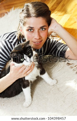 Portrait of a beautiful young woman lying on the floor, on a rug at home, cuddling her cat, smiling into camera - stock photo