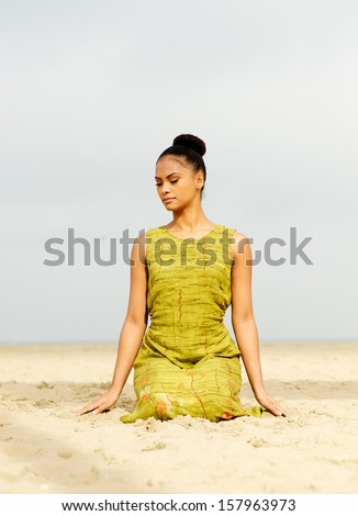 Portrait of a beautiful young woman meditating at the beach - stock photo