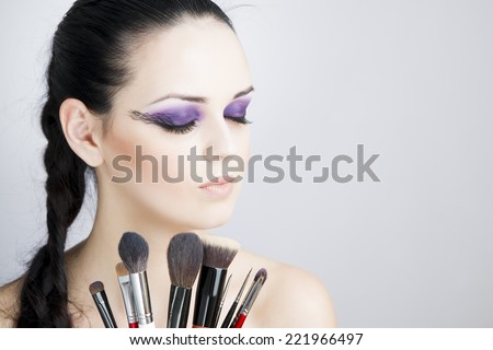 Portrait of a beautiful young woman on a gray background. Professional make-up and hairstyle. - stock photo