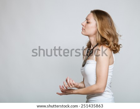Portrait of a beautiful young woman on gray background - stock photo
