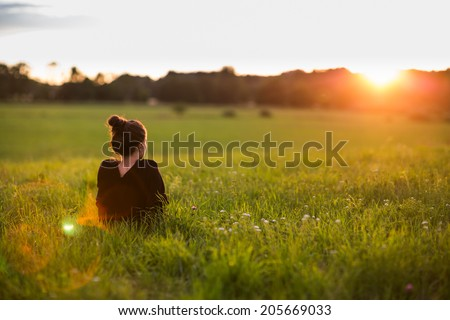 Portrait of a beautiful young woman or girl on very green meadow watching the sunset enjoying nature summer evening outdoors. Sunshine. Copy space. - stock photo