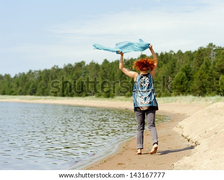 Portrait of a beautiful young woman outside running on the beach with a scarf - stock photo