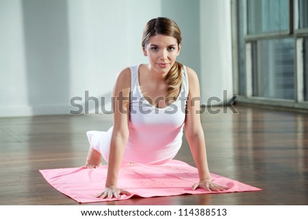 Portrait of a beautiful young woman practicing yoga on mat at gym - stock photo