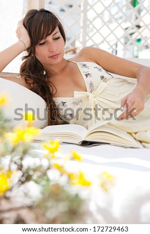 Portrait of a beautiful young woman relaxing and laying down on an exterior bed on a home terrace garden and reading a book while on holiday in a sunny summer city. Home exterior lifestyle. - stock photo