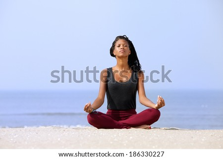 Portrait of a beautiful young woman sitting in yoga pose at the beach  - stock photo