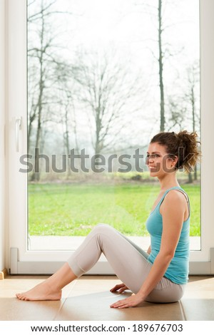 Portrait of a beautiful young woman sitting on the floor in her house near the window - stock photo