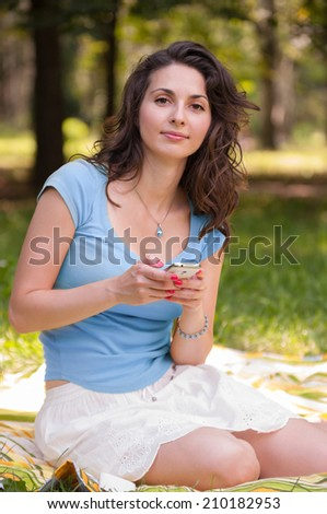 Portrait of a beautiful young woman sitting on the grass at park and chatting on phone, looking at the camera - stock photo