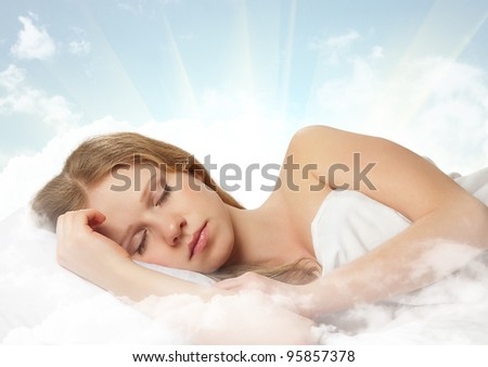 portrait of a beautiful young woman sleeping on a cloud in the sky - stock photo