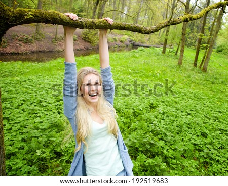 Portrait of a beautiful young woman smiling and hanging on a branch from a tree in the woods - stock photo