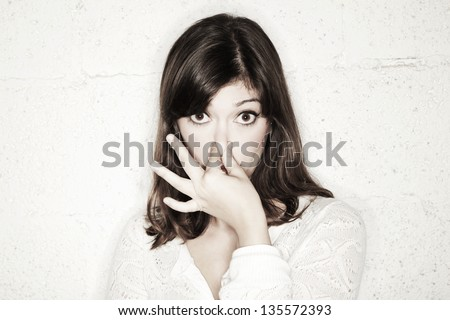 Portrait of a beautiful young woman staring into the camera with her eyes wide open and covering her nose with two fingers. Apparently something stinks. - stock photo