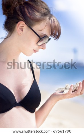Portrait Of A Beautiful Young Woman Studying Marine Life In The Form Of A Sea Star At An Outdoor Picturesque Beach Location - stock photo