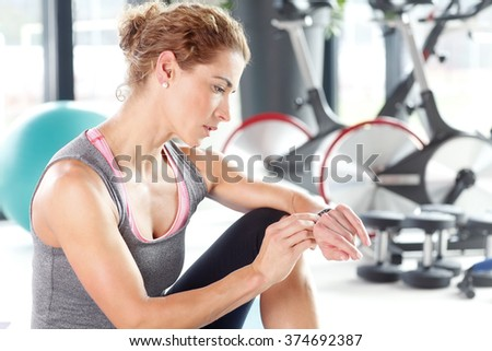 Portrait of a beautiful young woman taking a break after fitness workout and checking time.  - stock photo