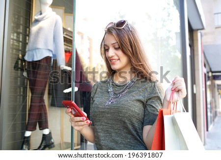 Portrait of a beautiful young woman using a smartphone standing by a fashion store display glass window with manikins, smiling with shopping bags on a sunny day. Consumer and technology lifestyle. - stock photo