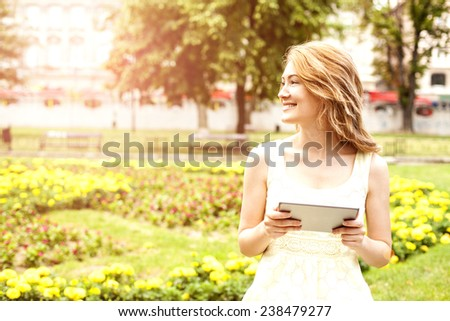 Portrait of a beautiful young woman using digital tablet, while relaxing in park.  - stock photo