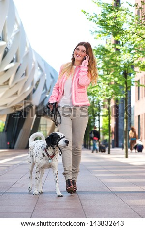 Portrait of a beautiful young woman walking her dog and talking to friends on mobile phone - stock photo