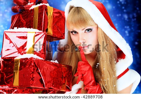 Portrait of a beautiful young woman wearing christmas clothes over sky of stars and snow. - stock photo