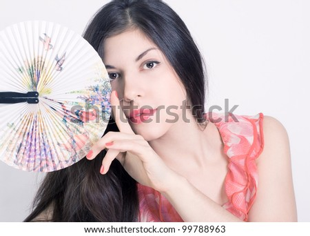 Portrait of a beautiful young woman with a fan. - stock photo