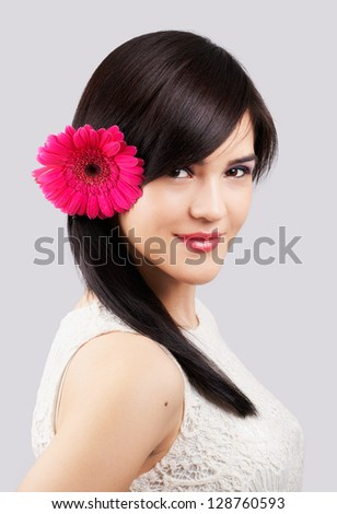 Portrait of a beautiful young woman with a flower in her hair isolated on grey - stock photo