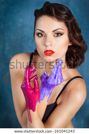 Portrait of a beautiful young woman with bright make up and colored hands - stock photo