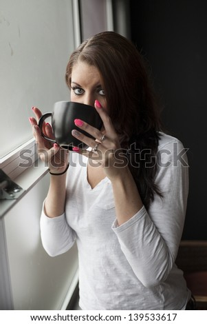 Portrait of a beautiful young woman with brown hair and blue eyes drinking from a black coffee cup. - stock photo