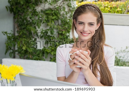 Portrait of a beautiful young woman with coffee and laptop at the caf�© - stock photo