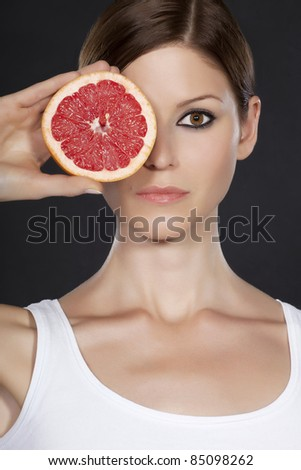 Portrait of a beautiful young woman with face partly covered by grapefruit - stock photo
