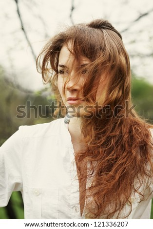 Portrait of a beautiful young woman with flying hair - stock photo