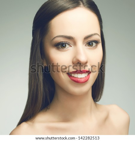 Portrait of a beautiful young woman with great white shiny smile posing over light-gray background. Healthy skin and teeth. Close up. Studio shot - stock photo