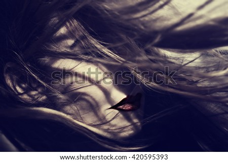 Portrait of a beautiful young woman with hair fluttering on the wind - stock photo