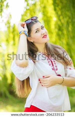 Portrait of a beautiful young woman with long brown hair who poses with sunglasses. The girl is on the nature and smiling.  - stock photo