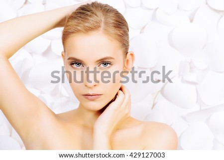 Portrait of a beautiful young woman with natural make-up over white floral background. Spa girl. Skincare, healthcare. Studio shot.  - stock photo